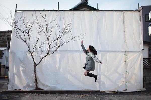 Frau schwebt vor einer Plane und streckt dabei die Hand zu einem Baum hoch