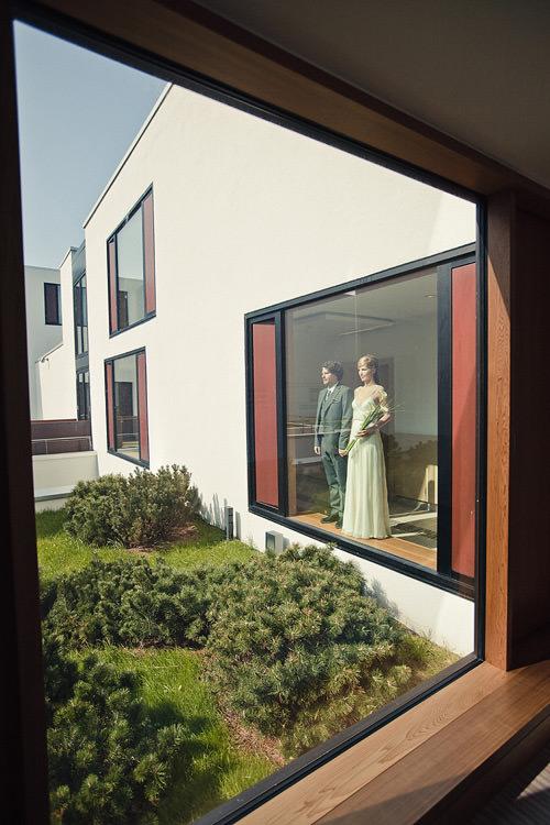Brautpaar steht hinter dem Fenster