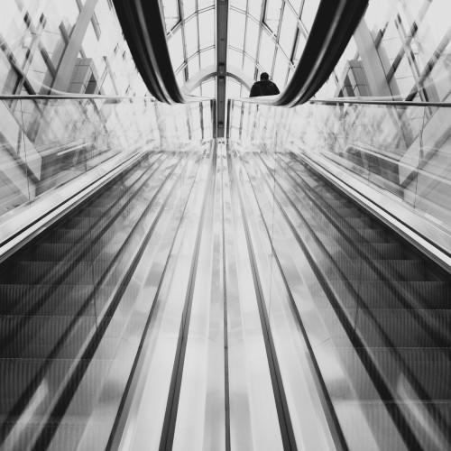 Hier ist eine Person auf einer Rolltreppe zu sehen. Diese ist jedoch nicht zu erkennen, sondern man sieht nur einen Kopf im Hintergrund.