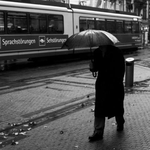 Hier sieht man einen Mann, der unter einem Schirm versteckt ist. Das Gesicht ist nicht zu erkennen, aber im Hintergrund ist eine Straßenbahn mit der Aufschrift 'Sehstörungen' und 'Sprachstörungen' zu sehen.