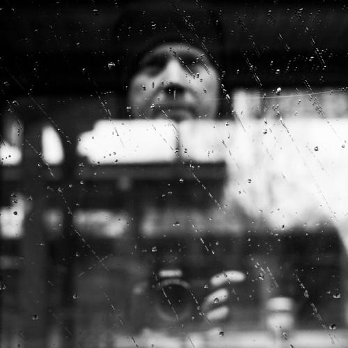 Unscharf ist Martin Gommel mit Kamera zu erkennen. Fotografiert wurde auf eine vom Regen nasse Glasscheibe.