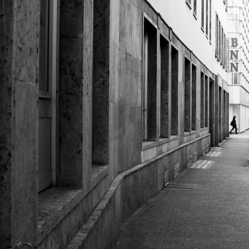 Dieses Foto zeigt eine Person, die sehr weit weg kurz davor ist, eine Straße zu überqueren. Sie ist am rechten Bildrand abgebildet und der Blick des Betrachters wird von links nach rechts an einer Hauswand zur Person geführt.