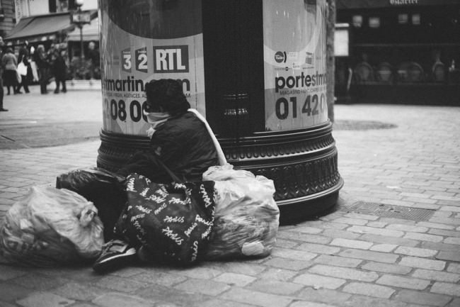 Ein obdachloser Mensch umgeben von Tüten