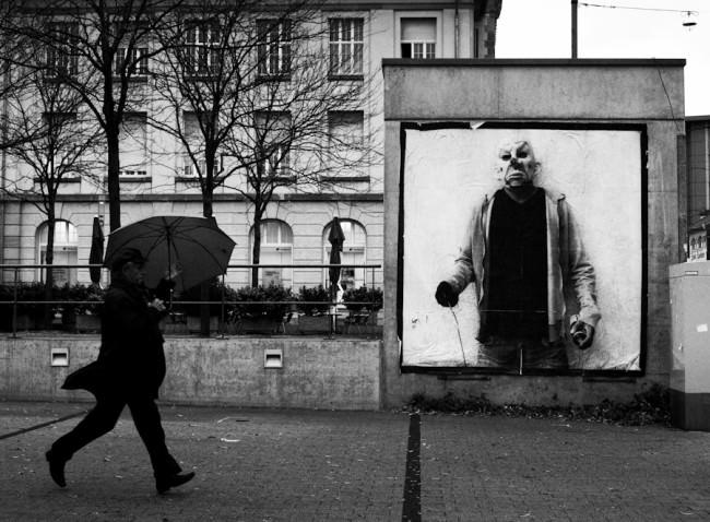 Ein Mensch läuft eilig mit dem Schirm zur Straßenbahn