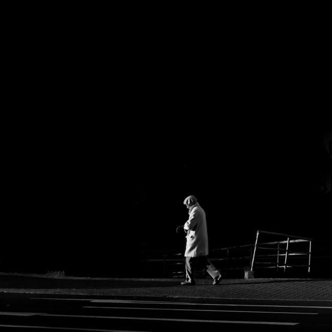 Person im Seitenlicht vor einem dunklen Hintergrund