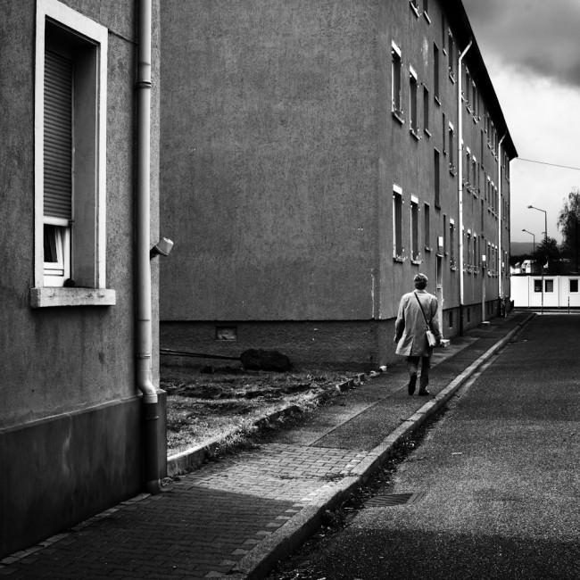Person von hinten fotografiert vor einer Häuserwand