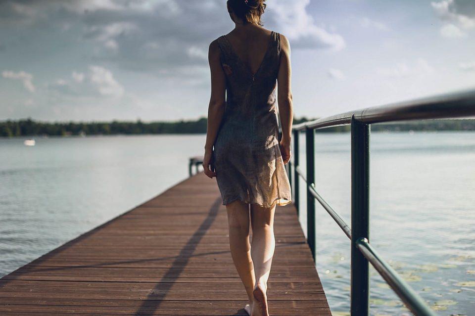 Frau geht auf einen Steg