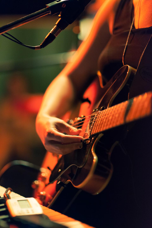 Foto auf Sóleys Hände fokussiert - sie liegen an der Gitarre an