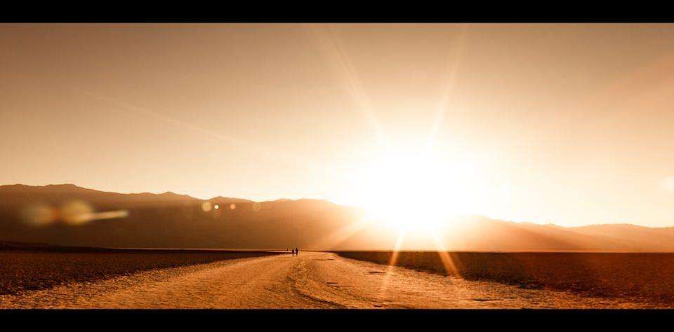 Foto, auf dem Menschen in einer Wüste der Sonne entgegenlaufen