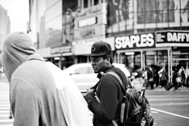 Ein junger Mensch mit Mütze, im Hintergrund unscharf städtischer Verkehr