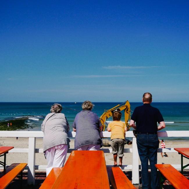 Ein kleiner Junge stützt sich zwischen drei Erwachsenen ab und schaut mit ihnen aufs Meer - im Vordergrund eine Baustelle