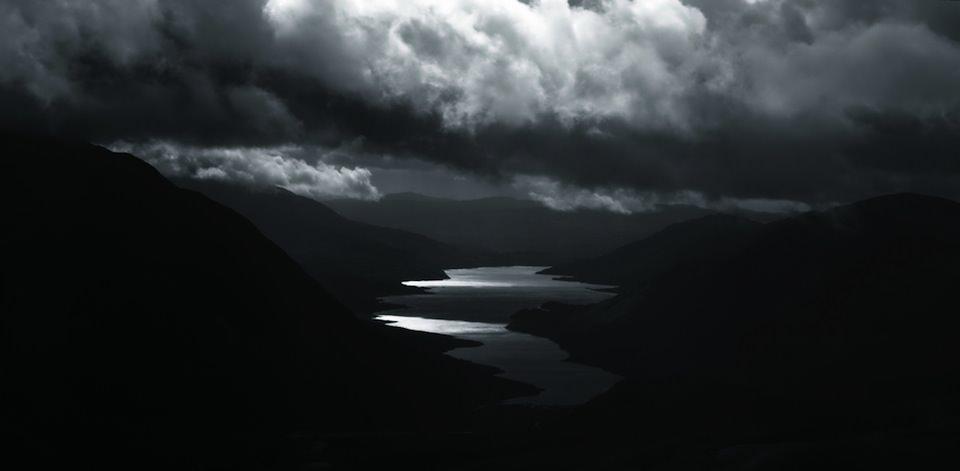Ein Blick auf eine dunkle Landschaft, über der viele Wolken zu sehen sind.