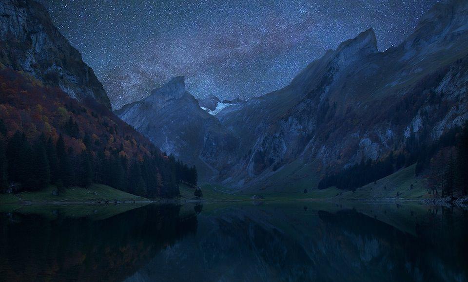 Du siehst eine Alpenlandschaft hinter einem See im Mondlicht