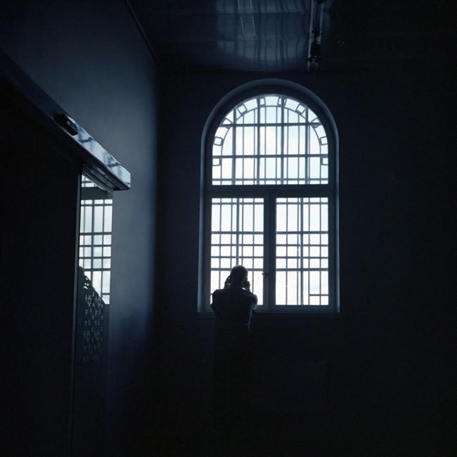 Ein Mann telefoniert und schaut dabei aus einem hohen Fenster