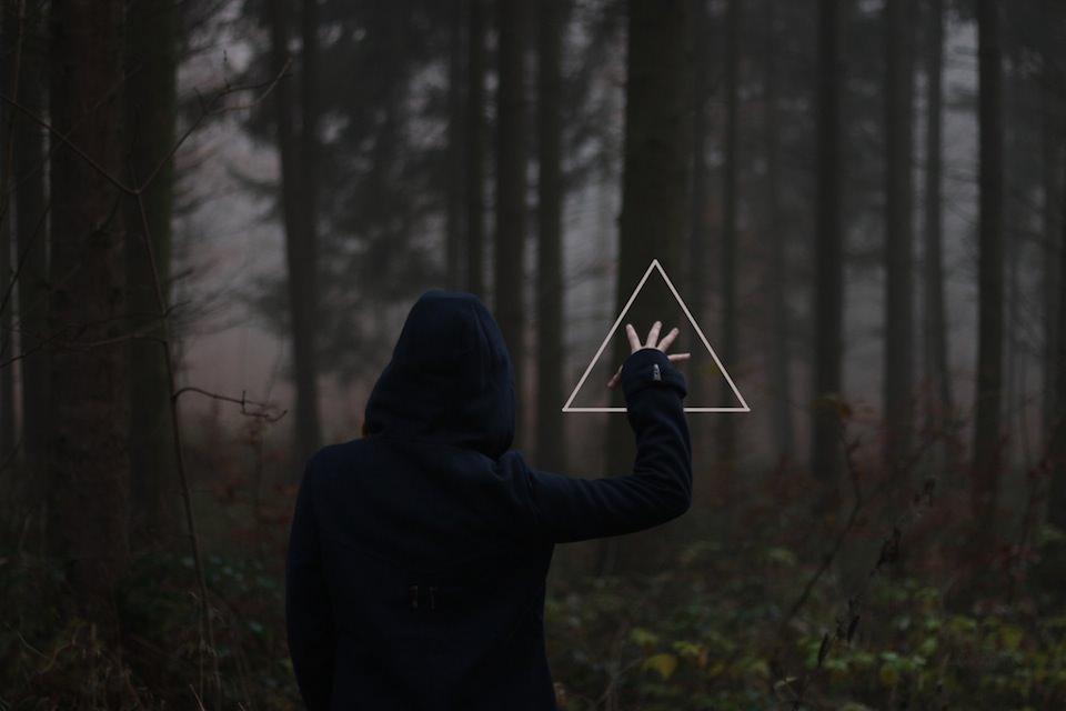 Foto von einem Menschen, der im Wald in ein Dreieck greift, surreal