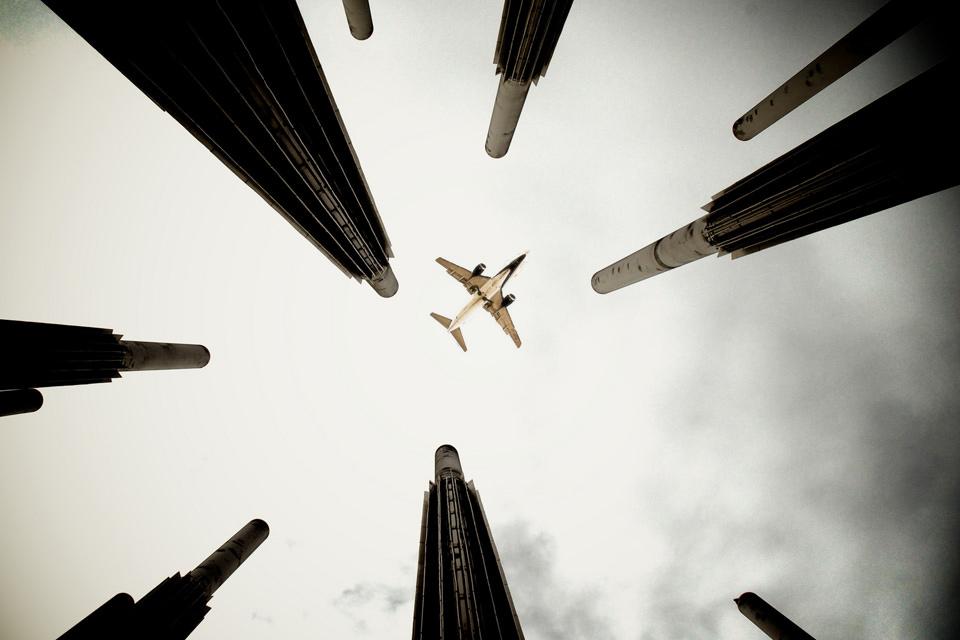 Ein Flugzeug über Schornsteinen.