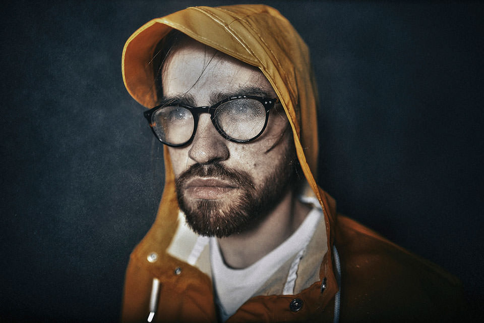 Portrait eines Mannes mit Regenjacke und Regenspritzern auf der Brille.