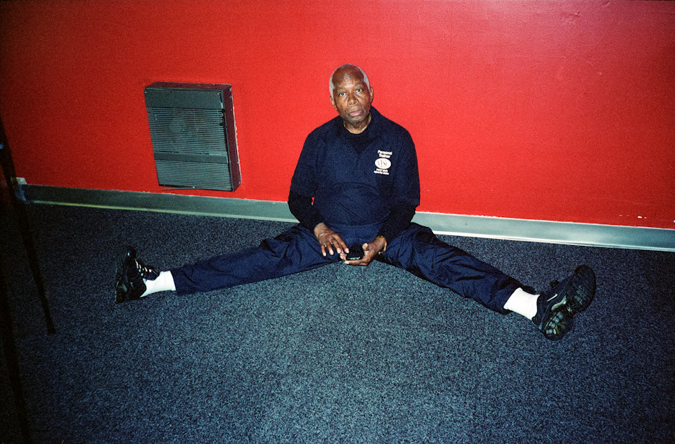 Ein Mann sitzt am Boden und hat die Beine weit gespreizt. New York City.