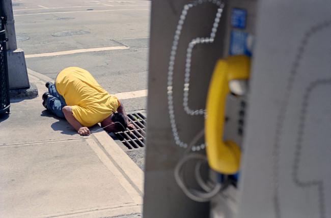 Straßenfotografie von Todd Gross: Ein Mann in gelbem T-Shirt schaut in einen Dohlen