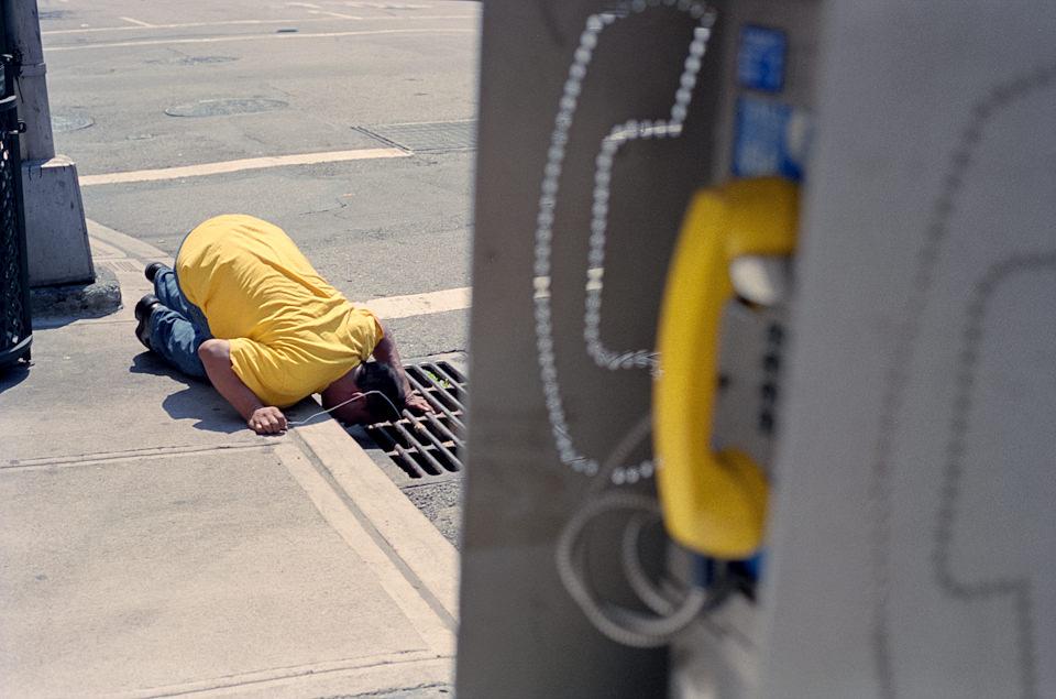 Straßenfotografie von Todd Gross: Ein Mann in gelbem T-Shirt schaut in einen Dohlen. New York City.