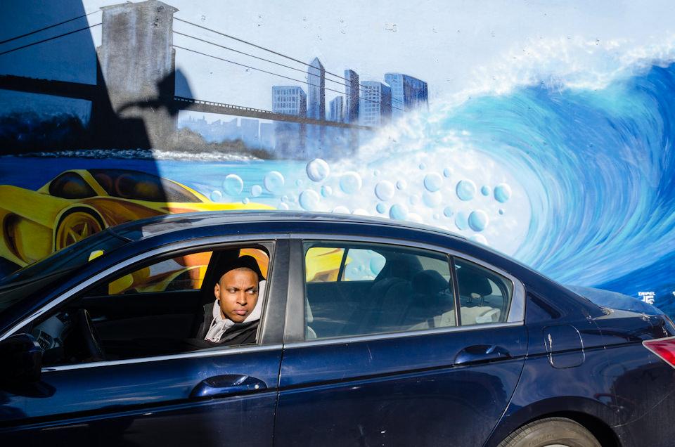 Eine Straßenfotografie von Todd Gross: Ein Autofahrer schaut aus dem Fenster, hinter ihm ist eine Welle zu sehen. New York City.