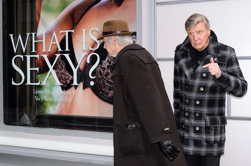 """Straßenfotografie von Todd Gross: Ein älterer Herr zeigt auf einen vorbeilaufenden Mann mit Hut undan der Wand hängt ein Poster, auf dem """"What Is Sexy"""" steht. New York City."""