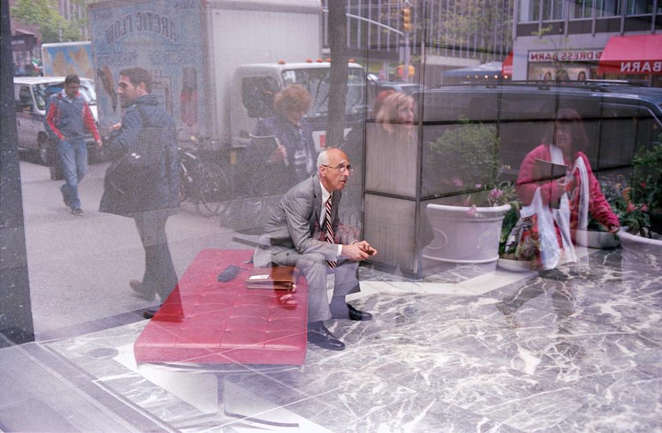 Straßenfotografie von Todd Gross: Das Portrait eines Mannes, der auf einer roten Banke sitzt, durch ein Fenster fotografiert. New York City.