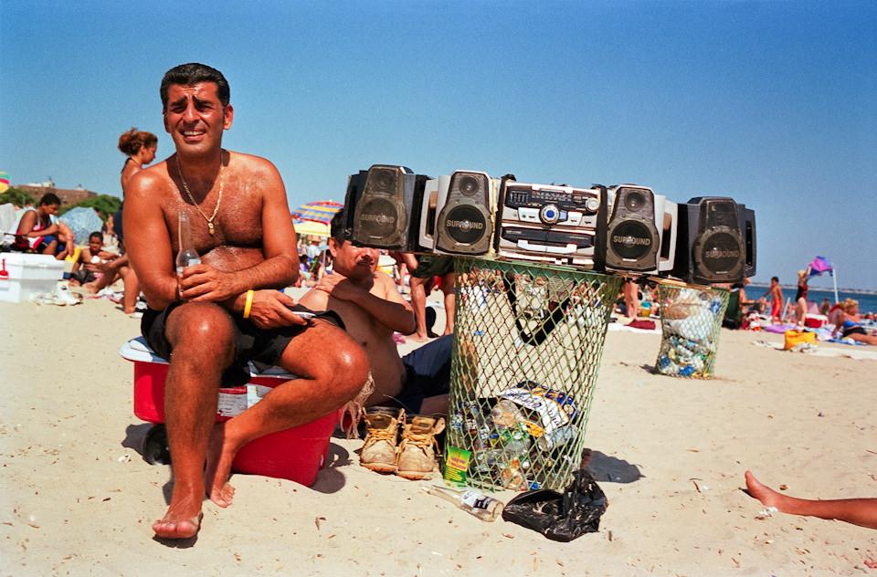 Straßenfotografie von Todd Gross: Ein Mann sitzt neben einem Ghettoblaster am Strand. New York City.