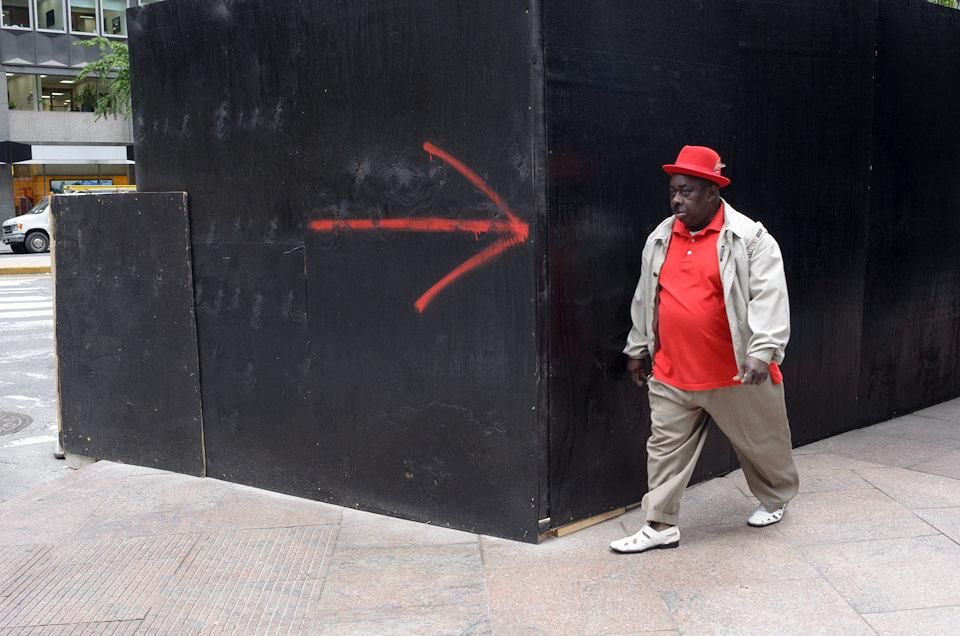 Straßenfotografie: Ein Mann in rotem T-Shirt und mit roter Kappe läuft um eine Ecke, an der ein roter Pfeil auf den Mann zeigt. New York City.