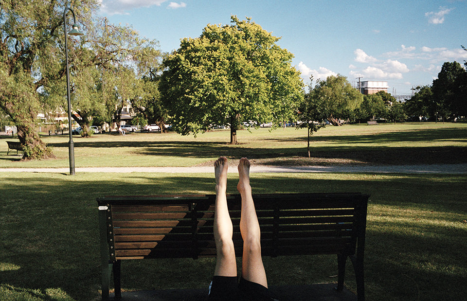Eine Frau hat ihre Beine hochgestreckt. Melbourne, Straßenfotografie von Jesse Marlow.