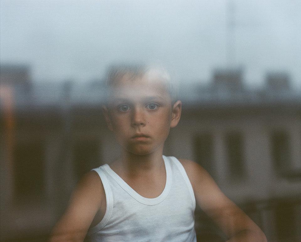 Ein Junge sieht aus dem Fenster.