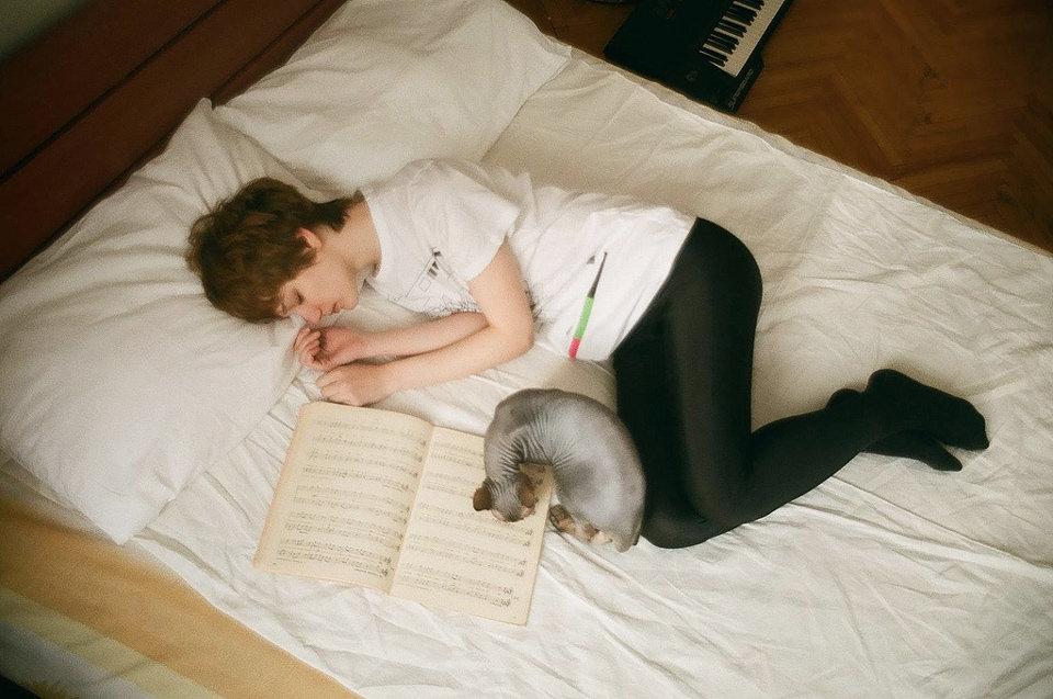 Eine Frau liegt mit ihrer Katze im Bett
