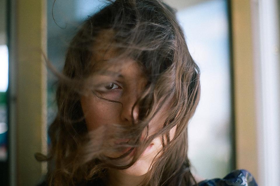 Blick in die Augen einer Frau, deren Haare quer über ihr Gesicht geweht sind.