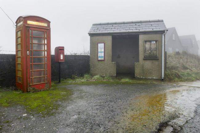 Eine Bushaltestelle, neben der noch eine Telefonzelle steht.