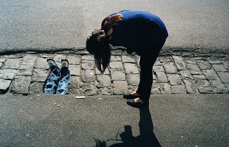 Eine Frau beugt sich und zwei Beine schauen unter Straße hervor. Melbourne, Straßenfotografie von Jesse Marlow.