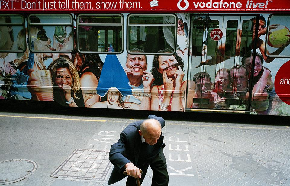 Ein Mann läuft gebückt auf die Kamera zu. Im Hintergrund steht ein Bus mit vielen Gesichtern drauf. Melbourne, Straßenfotografie von Jesse Marlow.