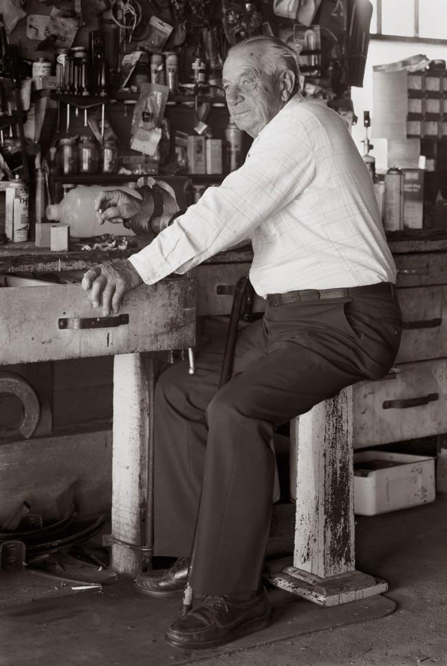 Eine Portraitfotografie, die einen alten Herrn auf einem Hocker zeigt, der ins Licht schaut.