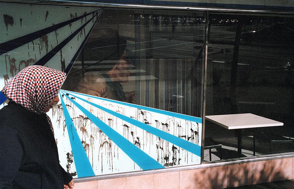 Eine Frau mit Kopftuch läuft direkt vor ein Fenster, das einen strahlenförmige Aufzug zeigt.Melbourne, Straßenfotografie von Jesse Marlow.