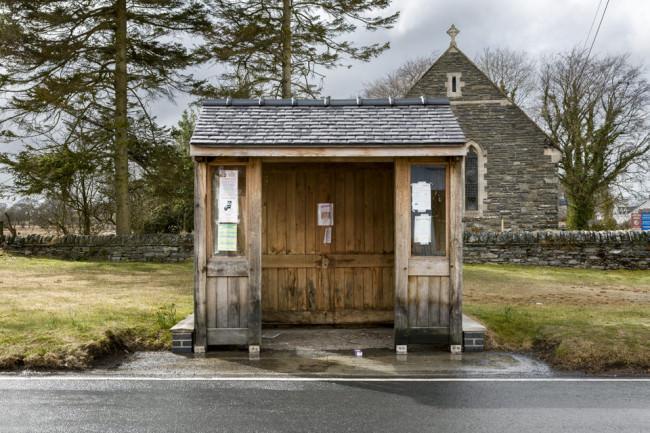 Eine Bushaltestelle bei Wales, die komplett aus Holz ist und vor einer Kapelle steht.