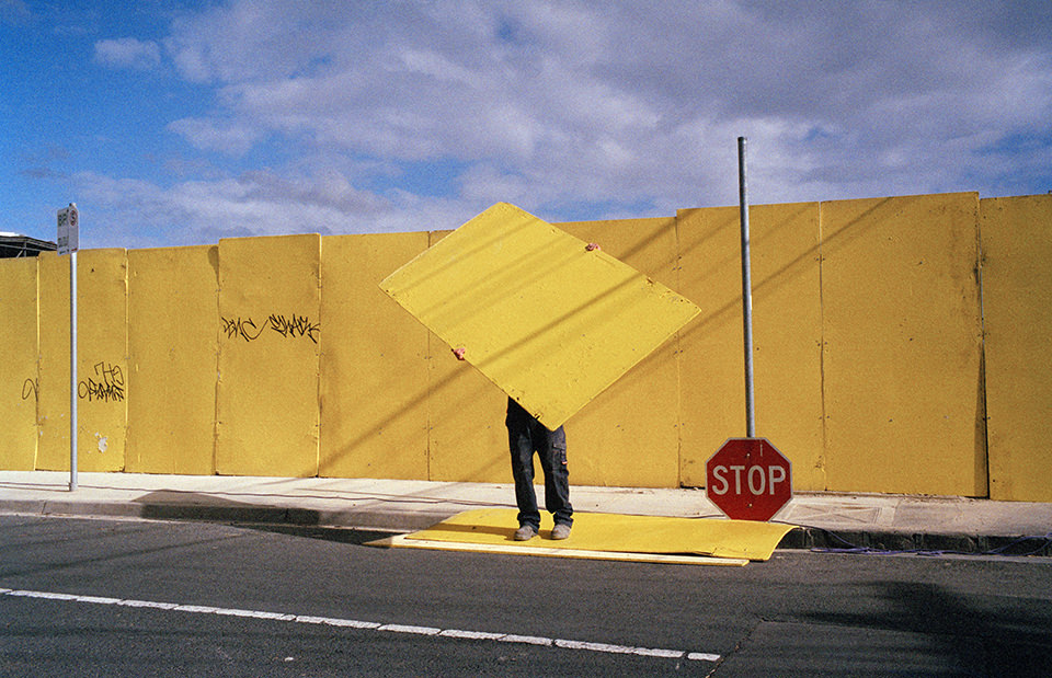 Ein Mensch hält ein gelbes Teil nach oben und steht auf der Straße vor einer gelben Wand. Melbourne, Straßenfotografie von Jesse Marlow.