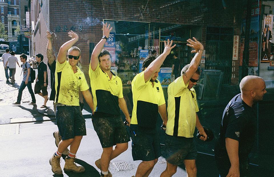 Viele Männer tragen eine Scheibe und halten ihre Hände komisch nach oben. Melbourne, Straßenfotografie von Jesse Marlow.