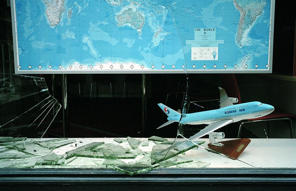 Wir sehen ein Flugzeug vor einer Landkarte in einem Reisbüro, dessen Scheibe eingeschlagen wurde. Melbourne, Straßenfotografie von Jesse Marlow.