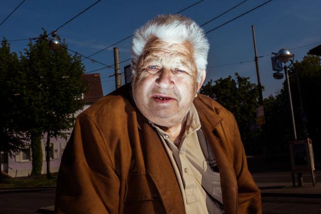 Ein älterer Herr guckt in die Kamera.