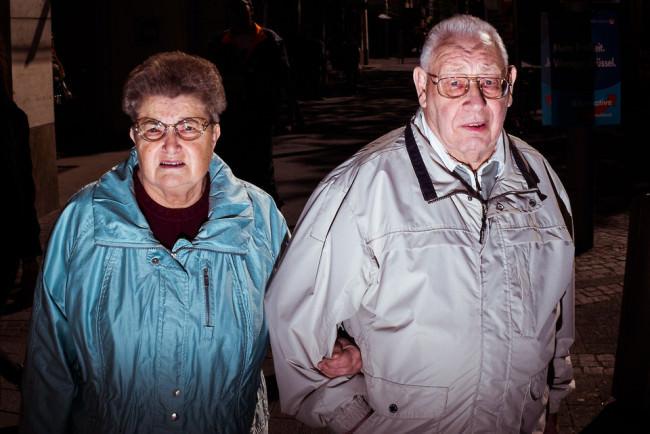 Zwei alte Menschen, einander eingehakt.