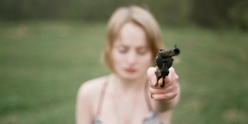 Eine Frau zielt mit der Pistole neben der Kamera mit verschlossenen Augen vorbei. Eine Portraitfotografie