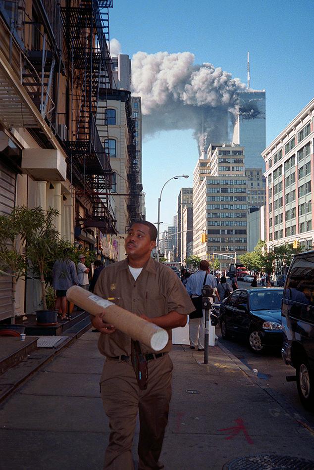Ein Postbote läuft am 11. September die Straße entlang, im Hintergrund brennen die zwei Türme.
