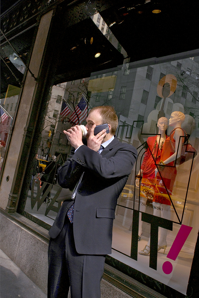 Ein Mann telefoniert mit der einen und trinkt mit der anderen Hand einen Kaffee, Hände dabei überkreuzt.