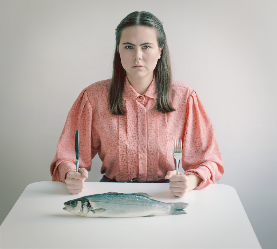 Portrait: Eine Frau sitzt mit Messer und Gabel am Tisch und guckt in die Kamera.