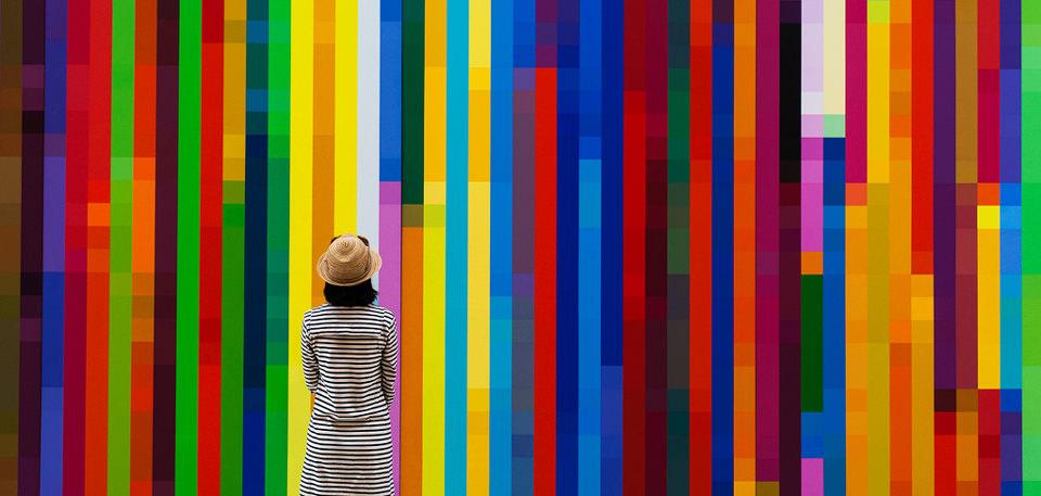 Eine Frau steht vor einer Wand, die aus Streifen besteht.