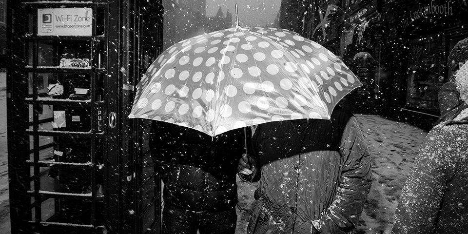 Eine Straßenfotografie mit einem Schirmträger, es schneit.